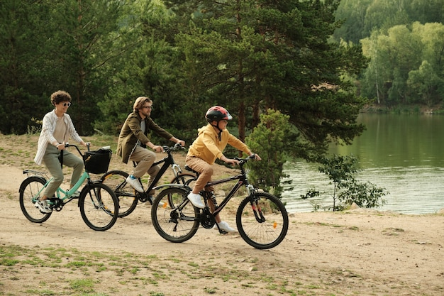 Contemporary happy family of three in casualawear sitting on bicycles while moving along riverside while enjoying active rest together