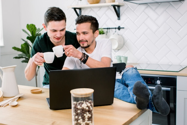 Contemporary homosexual couple sitting by table at kitchen home in front of laptop and watching online news. happy gay couple in jeans and t-shirts spending time together
