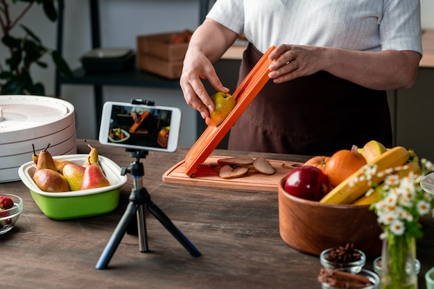 Contemporary housewife or blogger standing by kitchen table in front of smartphone camera and recording video of making dry fruit
