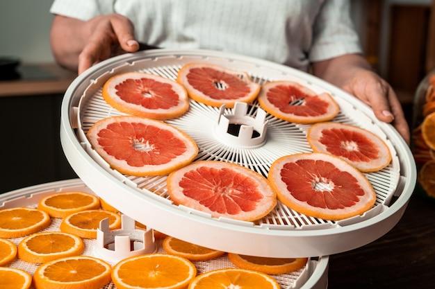 現代の主婦は台所のテーブルのそばに立って、オレンジスライスでその上にスライスされたグレープフルーツとフルーツドライヤートレイを置きます
