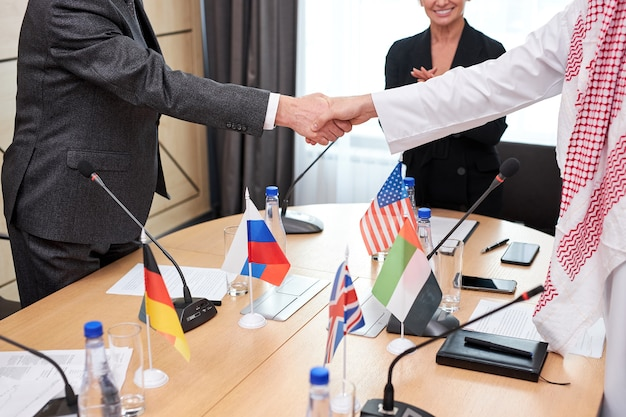 Contemporary intercultural delegates shaking hands after successful meeting press conference with microphones, in boardroom office. caucasian and arabic executives signed a bilateral agreement