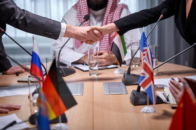 Contemporary intercultural delegates shaking hands after successful meeting press conference with microphones, in boardroom office. executives signed a bilateral agreement