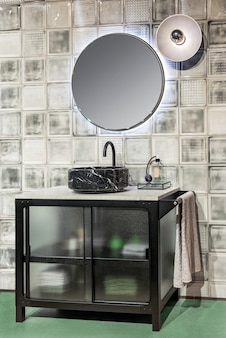 Contemporary interior of bathroom with black marble sink and illuminated round shaped mirror hanging on tiled wall