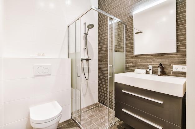 Современный дизайн интерьера ванной комнаты со стеклянной душевой кабиной и стильным шкафом с раковиной у кафельной стены и с белым туалетом.