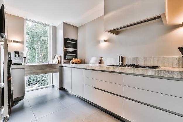ミニマリストスタイルの灰色のキャビネットに石のカウンターとオープンプランのキッチンの現代的なインテリアデザイン