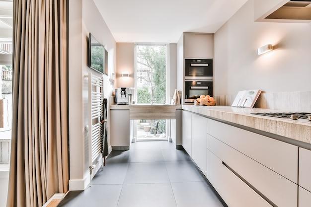 미니멀 스타일의 회색 캐비닛에 돌 카운터가있는 개방형 주방의 현대적인 인테리어 디자인