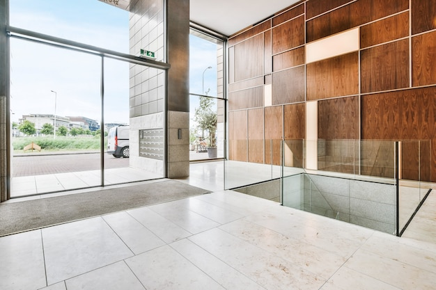 大きな窓と明るい大理石の床、幾何学的な木製の壁の装飾が施された広々としたホールの現代的なインテリアデザイン