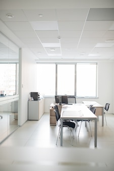 Contemporary interior of empty office room with long table, chairs and desk with computer