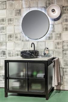 Современный интерьер ванной комнаты с раковиной из черного мрамора и круглым зеркалом с подсветкой, висящим на кафельной стене.