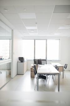 長いテーブル、椅子、コンピューターと机のある空のオフィスルームの現代的なインテリア