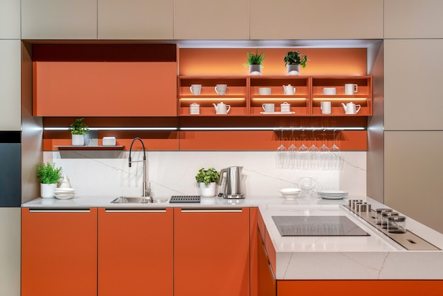 오렌지 색상의 미니멀한 스타일로 디자인된 주방 가전 및 찬장의 현대적인 인테리어
