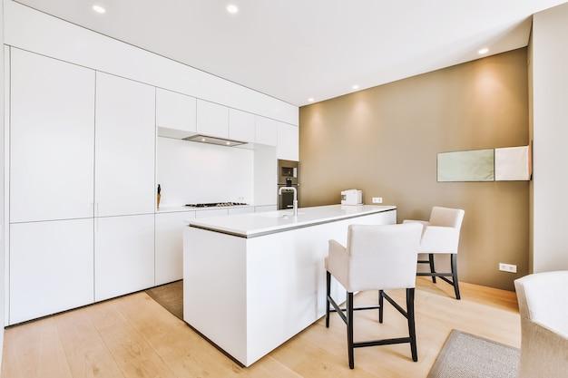 Современный интерьер кухни с белой мебелью и светильниками в стиле минимализм.