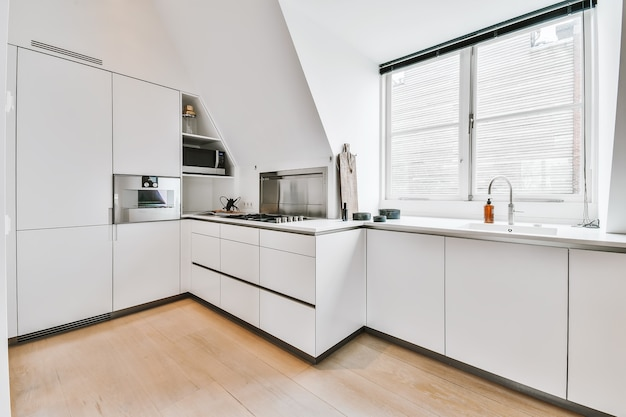 Contemporary kitchen interior with white cabinets and shiny appliances in apartment with mansard roof and window