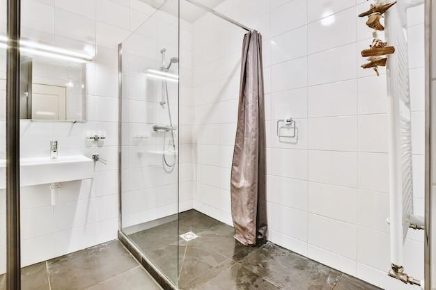 ガラス張りのシャワーキャビンと照明付きの鏡の下にある白い洗面器を備えた現代的な豪華な洗面所