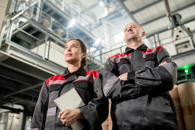 Современные инженеры-мужчины и женщины в спецодежде стоят перед камерой на фоне огромного технического сооружения на большом складе
