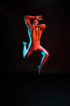 Contemporary male ballet dancer performing in spotlight