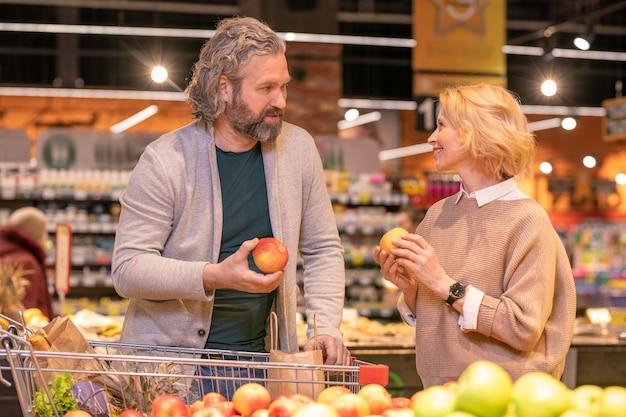 Современная зрелая пара с тележкой для покупок обсуждает сорта яблок в супермаркете, выбирая свежие фрукты и другие продукты