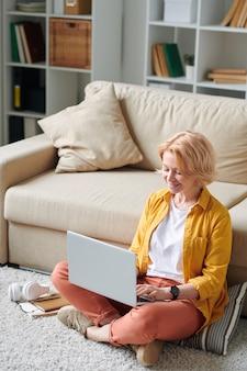 検疫でリモートで作業しながらソファで床に座っているラップトップを持つ現代の成熟した足を組んだ実業家