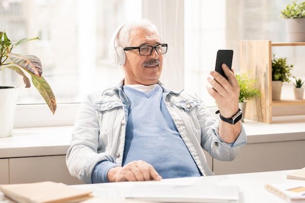 カジュアルウェアとヘッドフォンでオフィスに座っている間スマートフォンでビデオを見て現代の成熟したモバイル男