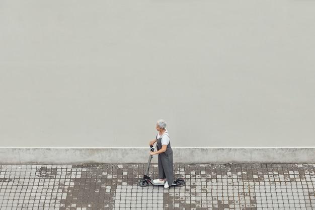 Современная зрелая женщина на скутере