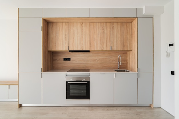 Современная минималистичная кухня в пустой отремонтированной квартире, деревянная мебель и современная техника