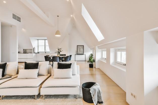 白い壁とロフトスタイルの屋根裏部屋のオープンスペースのアパートのソファとカーペットのあるラウンジゾーンの現代的なミニマリストのインテリアデザイン