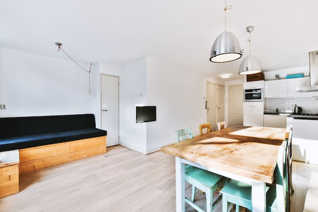Contemporary minimalist style interior design of light studio apartment with wooden table and chairs in dining zone between open kitchen and living room with white walls and parquet floor