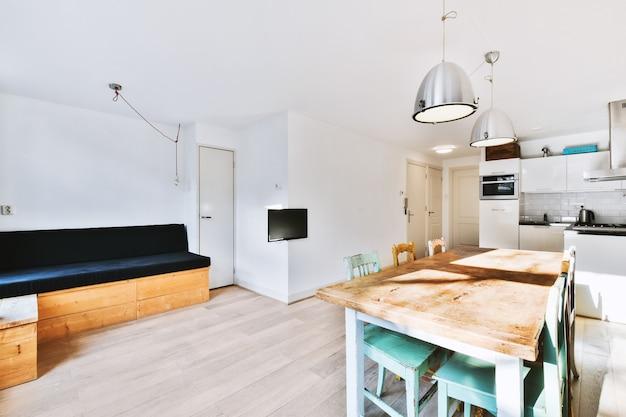 Современный минималистичный дизайн интерьера светлой однокомнатной квартиры с деревянным столом и стульями в обеденной зоне между открытой кухней и гостиной с белыми стенами и паркетным полом.