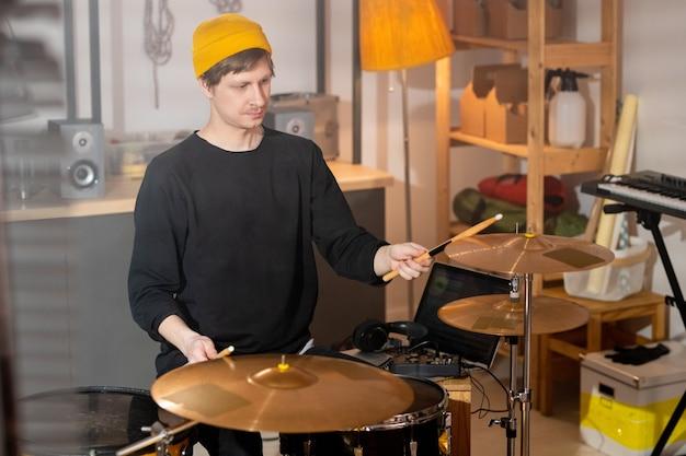 차고에서 드럼 키트로 리허설하면서 나무 나지만으로 심벌즈를 치는 캐주얼웨어를 입은 현대 음악가