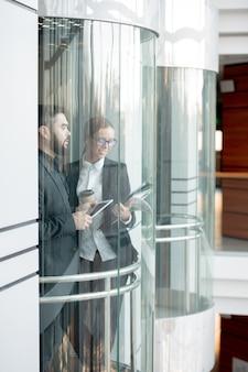 ガラス張りのエレベーターに立って、タブレットや紙の情報をチェックする正装の現代のオフィス従業員