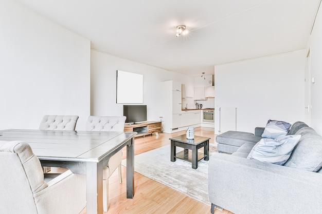 밝고 넓은 방에 식탁 세트와 회색 소파가있는 현대적인 오픈 플랜 주방