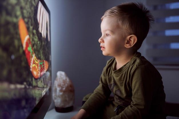 現代の子育て。テレビの前に座って漫画を見つめている少年のクローズアップショット。夜寝る前に子供を楽しませる。子供を寝かせる前の儀式
