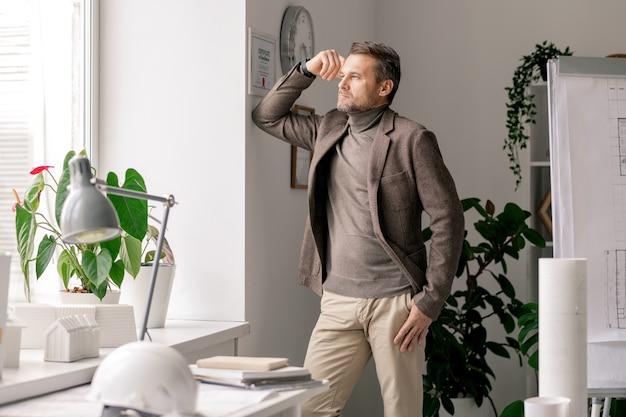 Современный задумчивый архитектор или менеджер в строгой одежде смотрит в окно офиса во время перерыва