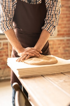 Современный гончар в спецодежде стоит у деревянного стола и месит глину на стопке досок в мастерской