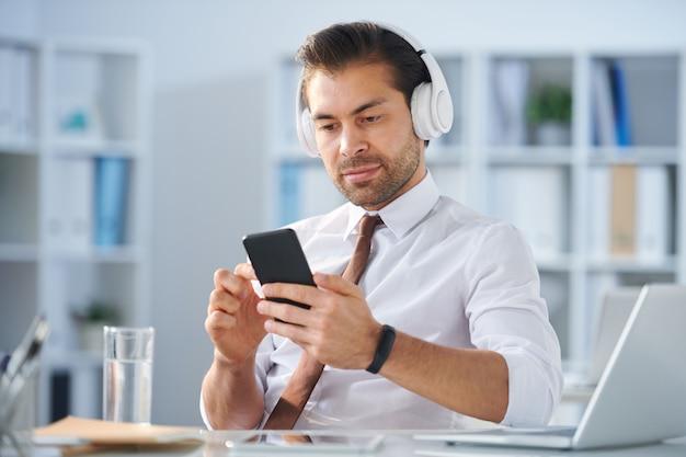 Современный спокойный бизнесмен в наушниках выбирает саундтрек из плейлиста в смартфоне во время перерыва