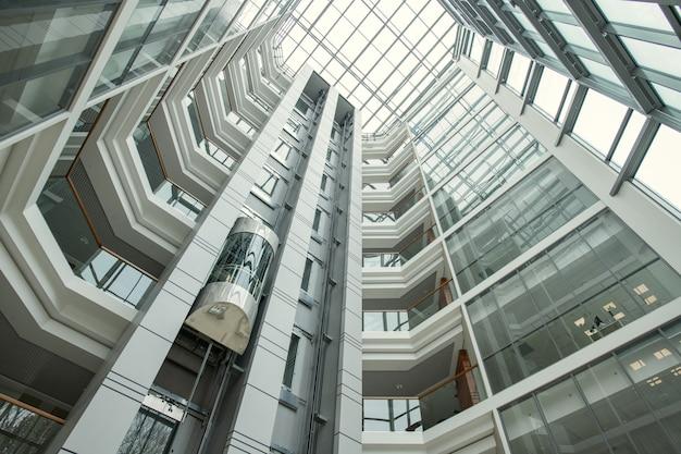 エレベーターが上に移動し、ガラスの壁と現代的な丸い形のオフィスのインテリア