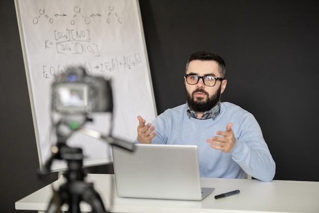 Contemporary school teacher in pullover and eyeglasses explaining something to his students during remote lesson of chemistry