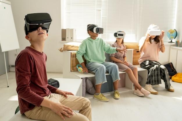ビデオプレゼンテーションを見ている現代の男子生徒と彼のクラスメート