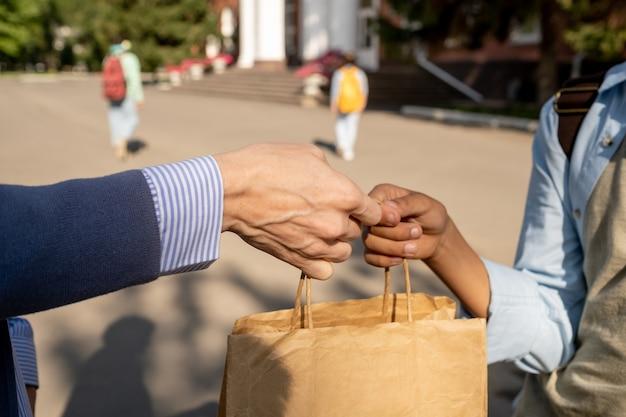 Современный школьник берет бумажный пакет с едой на обед