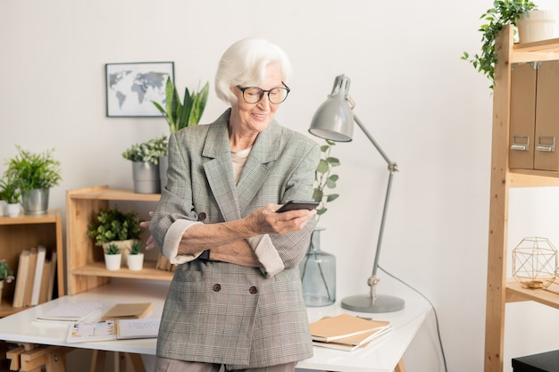 Contemporary senior businesswoman with smartphone standing by desk while messaging or reading notification in the gadget