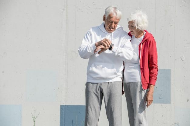 Contemporary  senior couple using smartwatch