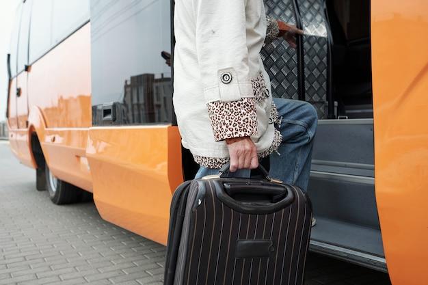 Современный старший пассажир с чемоданом входит в автобус