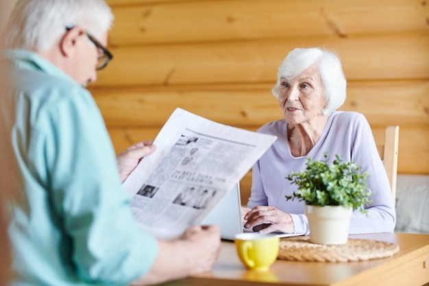Contemporary senior wife networking and looking at her husband reading latest news in front of her by table