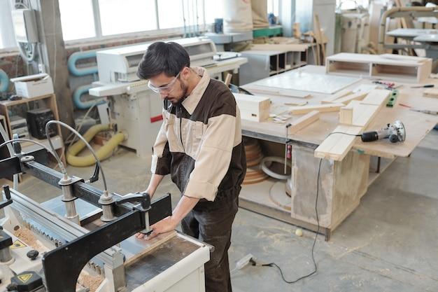 Современный старший рабочий фабрики смотрит на вас, наклоняясь над промышленным станком для обработки дерева против интерьера мастерской