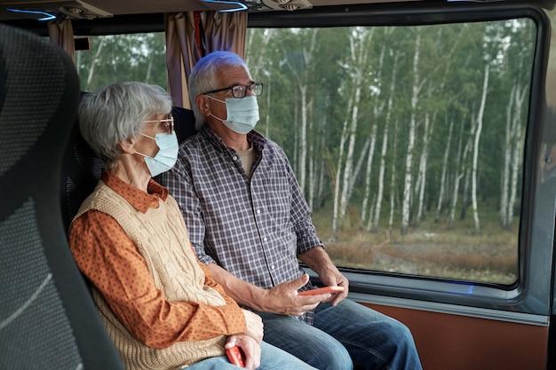 Современные пожилые люди в защитных масках на автобусе