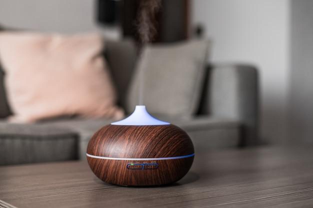 居心地の良い部屋で水蒸気と保湿空気を放出するテーブル上の現代的なスマート加湿器