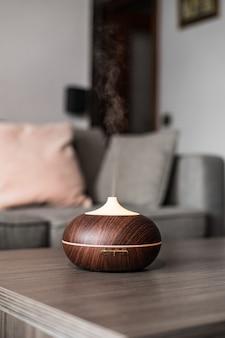 Современный умный увлажнитель воздуха на столе, испускающий водяной пар и увлажняющий воздух в уютной комнате