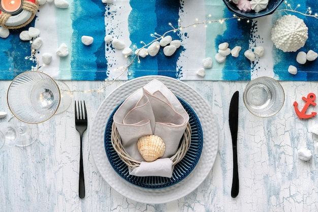 Contemporary summertime table setting with nautical sea decorations on blue and white stripy runner,