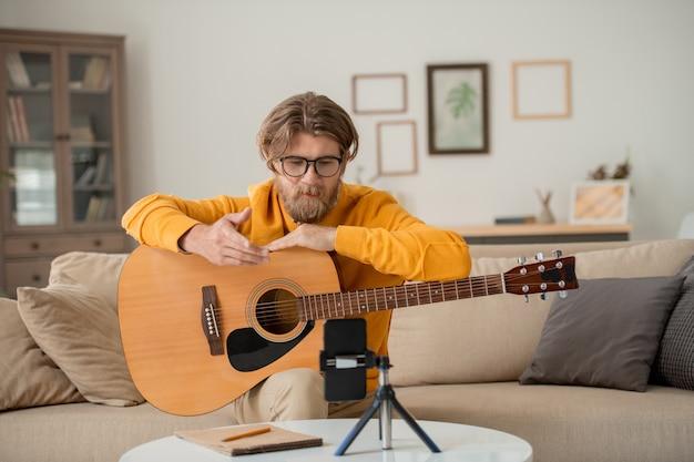 ギターを弾く現代の教師が、聴衆のために学習や紹介スピーチの主なルールを説明するオンラインコースを演奏しています