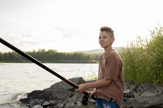 호숫가에서 혼자 낚시를 하는 긴 낚싯대를 가진 현대 10대 소년